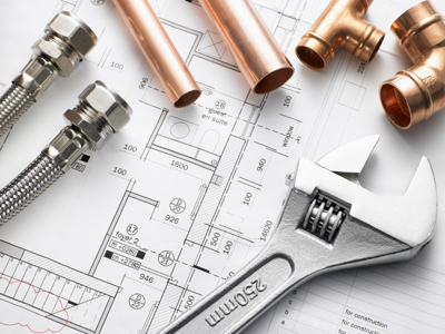 wrench, pipes and other tools laying on a blueprint