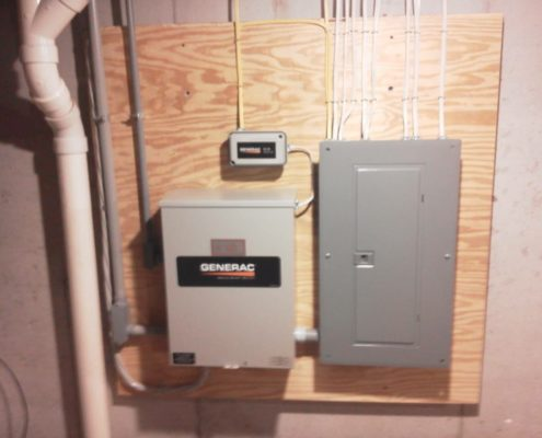 generac system on a wall next to a breaker box