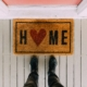 a welcome mat on the ground in front of a pink door that says Home with the O being a red heart